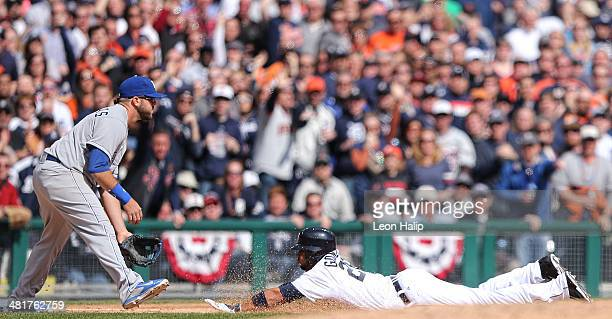 Alex Gonzalez of the Detroit Tigers slides into third base after hitting a triple to center field in the seventh inning scoring Alex Avila during the...