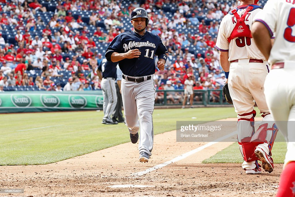 Alex Gonzalez #11 of the Milwaukee Brewers scores a run off of Jeff Bianchi's #14 RBI single in the ninth inning of the game against the Philadelphia Phillies at Citizens Bank Park on June 2, 2013 in Philadelphia, Pennsylvania. The Phillies won 7-5.