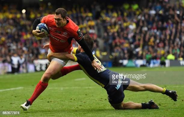 Alex Goode of Saracens hands off Morgan Parra of Clermont Auvergne to score his team's third try during the European Rugby Champions Cup Final...