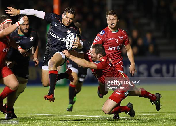 Alex Goode of Saracens is tacked by Ken Owens Captain of Scarlets during the European Rugby Champions Cup match between Saracens and Scarlets at...