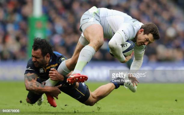Alex Goode of Saracens is tackled by Isa Nacewa during the European Rugby Champions Cup quarter final match between Leinster Rugby and Saracens at...
