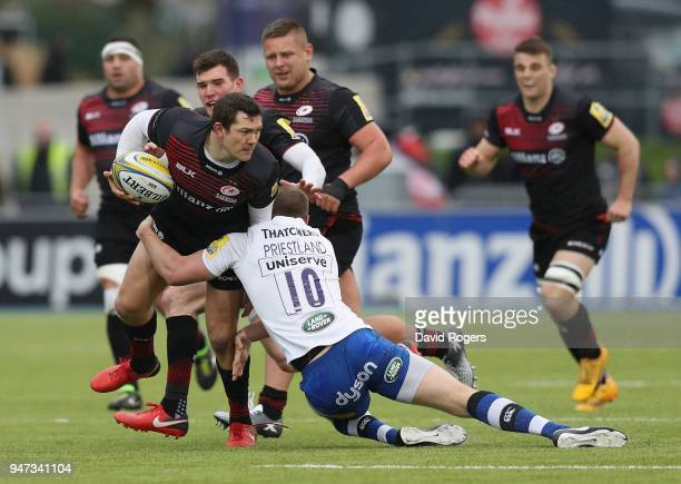 Alex Goode of Saracens is tackled by Rhys Priestland during the Aviva Premiership match between Saracens and Bath Rugby at Allianz Park on April 15...