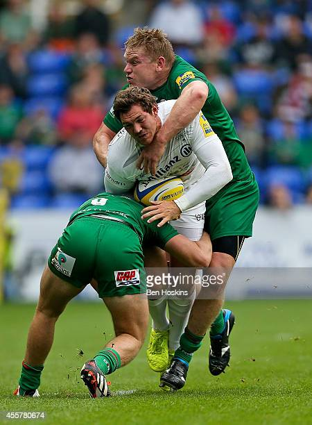 Alex Goode of Saracens is tackled by Scott Steele and Blair Cowan of London Irish during the Aviva Premiership match between London Irish and...
