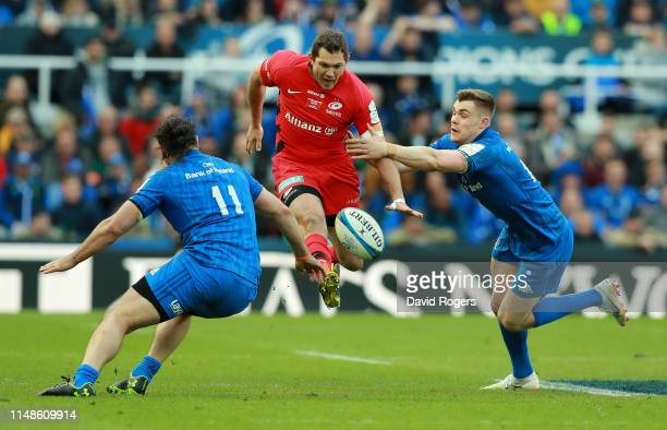Alex Goode of Saracens kicks the ball upfield past James Lowe and Garry Ringrose during the Champions Cup Final match between Saracens and Leinster...