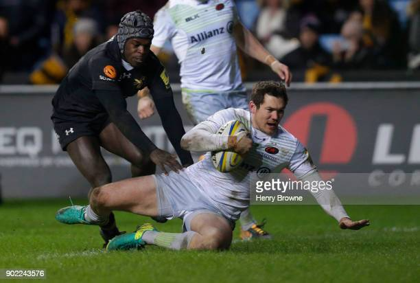 Alex Goode of Saracens scores a try despite the efforts of Christian Wade of Wasps during the Aviva Premiership match between Wasps and Saracens at...