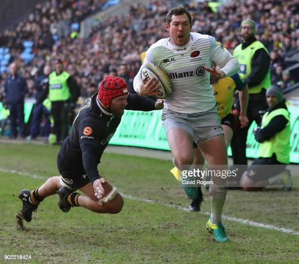 Alex Goode the Saracens fullback breaks clear of James Haskell to score their second try during the Aviva Premiership match between Wasps and...