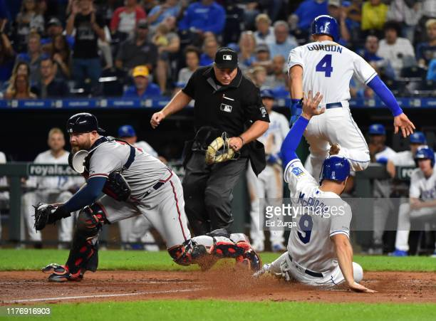 Alex Gordon and Ryan McBroom of the Kansas City Royals score against catcher Brian McCann of the Atlanta Braves on a Bubba Starling three-run double...