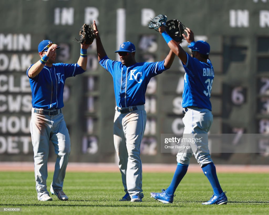 Alex Gordon #4 (L), Drew Butera #9 (C), and Jorge Bonifacio #38 (R) of the Kansas City Royals celebrate in the outfield after winning the game against the Boston Red Sox at Fenway Park on July 30, 2017 in Boston, Massachusetts.