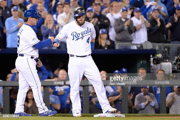 Alex Gordon of the Kansas City Royals bumps fists with third base coach Mike Jirschele during Game 6 of the 2014 World Series against the San...