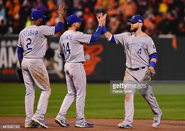 Alex Gordon of the Kansas City Royals celebrates with his teammates Omar Infante and Alcides Escobar after defeating the Baltimore Orioles 8 to 6 in...
