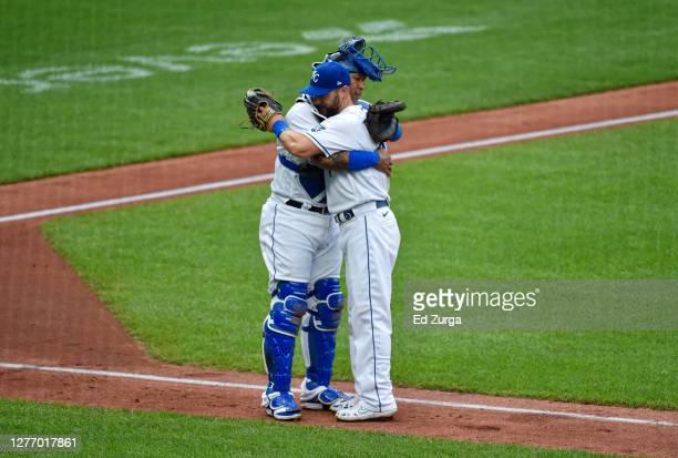 Alex Gordon of the Kansas City Royals hugs catcher Salvador Perez as he exits in his last career game during play against the Detroit Tigers in the...