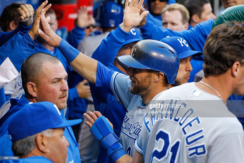 Alex Gordon #4 of the Kansas City Royals is congratulated by teammates after scoring a run in the fifth inning of the Opening Day game against the Philadelphia Phillies at Citizens Bank Park on April 5, 2013 in Philadelphia, Pennsylvania. The Royals won 13 to 4.