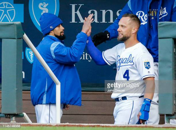 Alex Gordon of the Kansas City Royals is greeted by Billy Hamilton after Gordon scored on a two run triple by Hunter Dozier in the third inning...