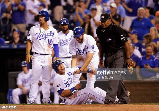 Alex Gordon of the Kansas City Royals is helped up by Mike Moustakas after stumbling over home plate as he scores on a three RBI double by Whit...