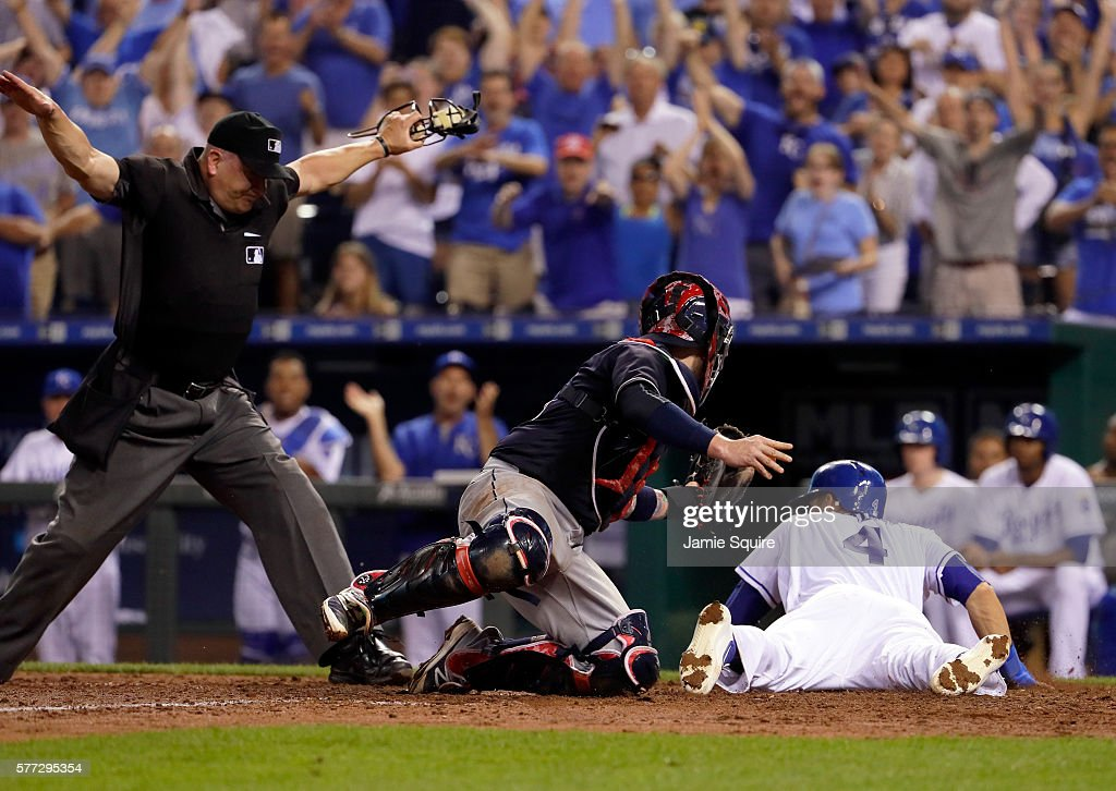 Alex Gordon #4 of the Kansas City Royals slides safely into home plate to score s Roberto Perez #55 of the Cleveland Indians is late applying the tag during the 8th inning of the game at Kauffman Stadium on July 18, 2016 in Kansas City, Missouri.