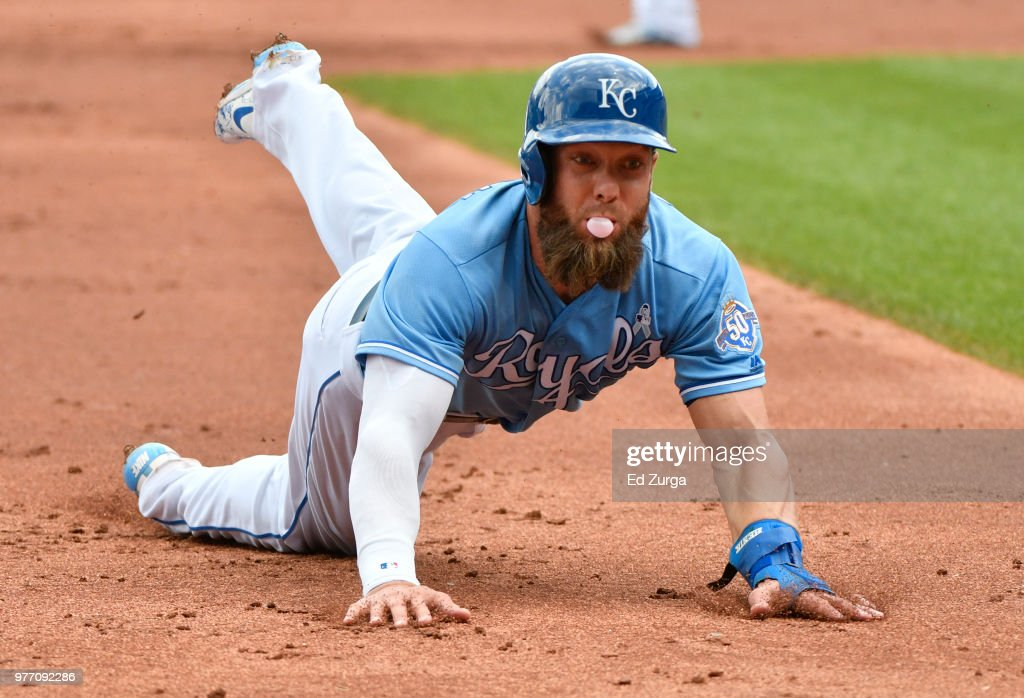 Alex Gordon #4 of the Kansas City Royals slides safely into third base on a Salvador Perez single in the first inning at Kauffman Stadium on June 17, 2018 in Kansas City, Missouri.