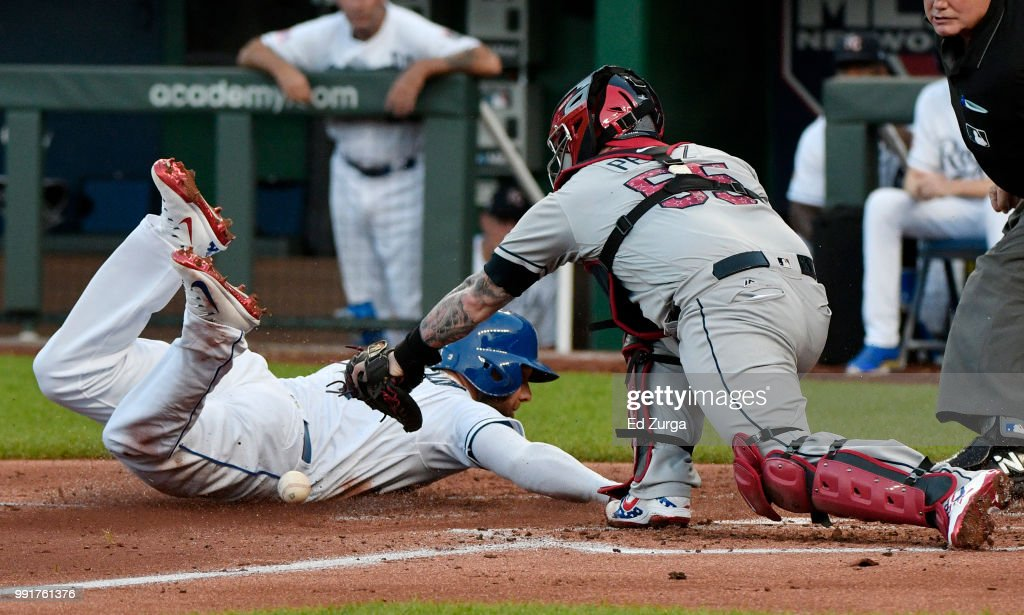 Alex Gordon #4 of the Kansas City Royals steals home past Roberto Perez #55 of the Cleveland Indians in the second inning at Kauffman Stadium on July 4, 2018 in Kansas City, Missouri.