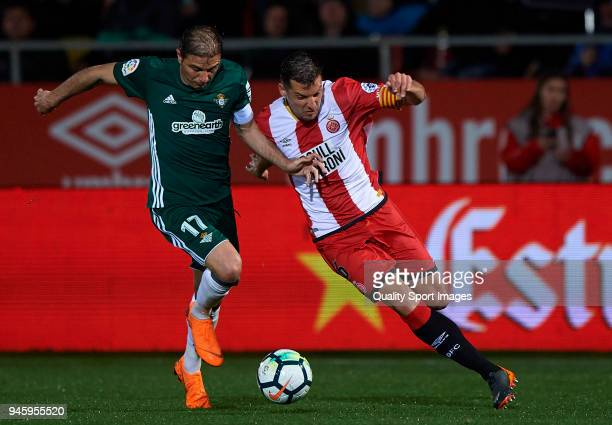 Alex Granell of Girona competes for the ball with Joaquin Sanchez of Real Betis during the La Liga match between Girona and Real Betis at Estadi...