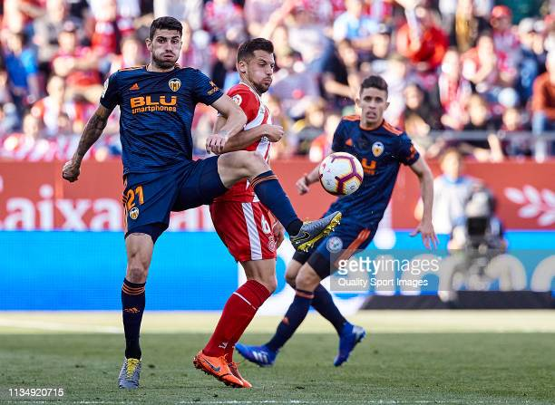 Alex Granell of Girona FC competes for the ball with Cristiano Piccini of Valencia CF during the La Liga match between Girona FC and Valencia CF at...