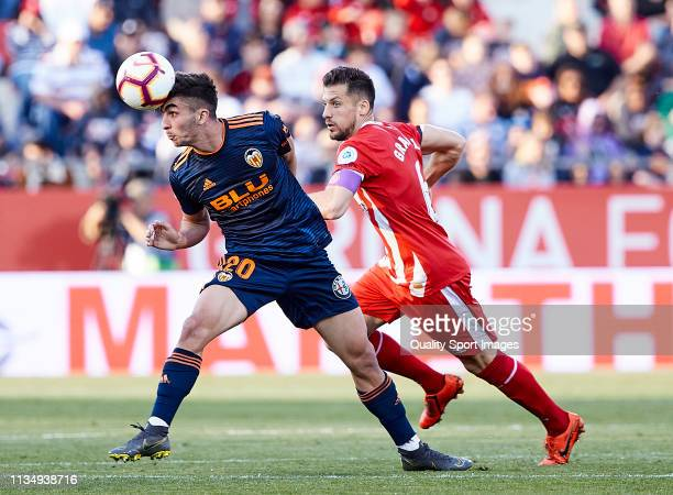 Alex Granell of Girona FC competes for the ball with Ferran Torres of Valencia CF during the La Liga match between Girona FC and Valencia CF at...