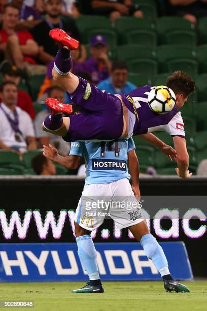 Alex Grant of the Glory crashes over Daniel Arzani of Melbourne in a contest for the ball during the round 15 ALeague match between the Perth Glory...