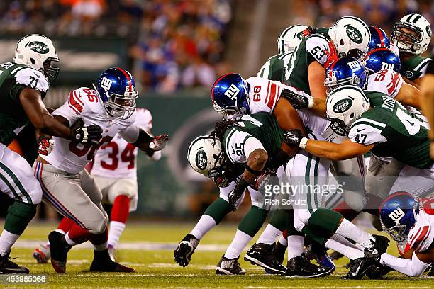 Alex Green of the New York Jets is tackled by Kerry Wynn of the New York Giants during the fourth quarter of a preseason game at MetLife Stadium on...
