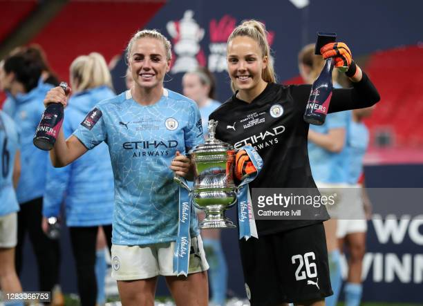 Alex Greenwood of Manchester City and Ellie Roebuck of Manchester City celebrate with the Vitality Women's FA Cup Trophy following their team's...