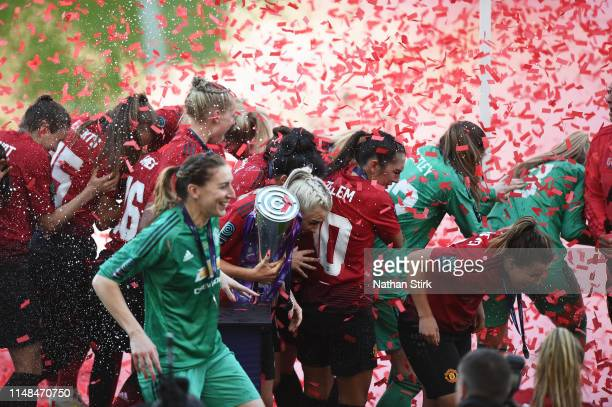 Alex Greenwood of Manchester United Women protects the trophy after confetti during the Women's Super League match between Manchester United Women...