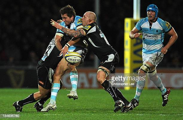 Alex Grove of Worcester is tackled by Jason Shoemark and James Scaysbrook of Exeter during the AVIVA Premiership match between match between Exeter...