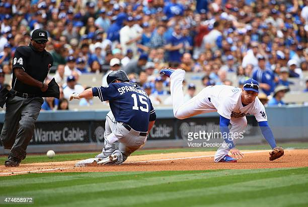 Alex Guerrero of the Los Angeles Dodgers can't catch the cut off throw to third base as Cory Spangenberg of the San Diego Padres slides into third...