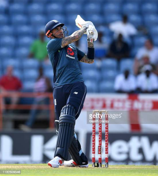 Alex Hales of England hits out for six runs during the 4th One Day International match between the West Indies and England at Grenada National...