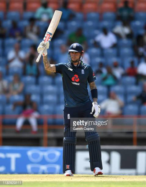 Alex Hales of England raises his bat after making 50 runs during the 4th One Day International match between the West Indies and England at Grenada...
