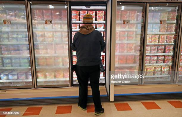 Alex Halstead works on the ice cream display as preparations take place for the opening of the new Market Basket store in Lynn MA on Aug 25 2017