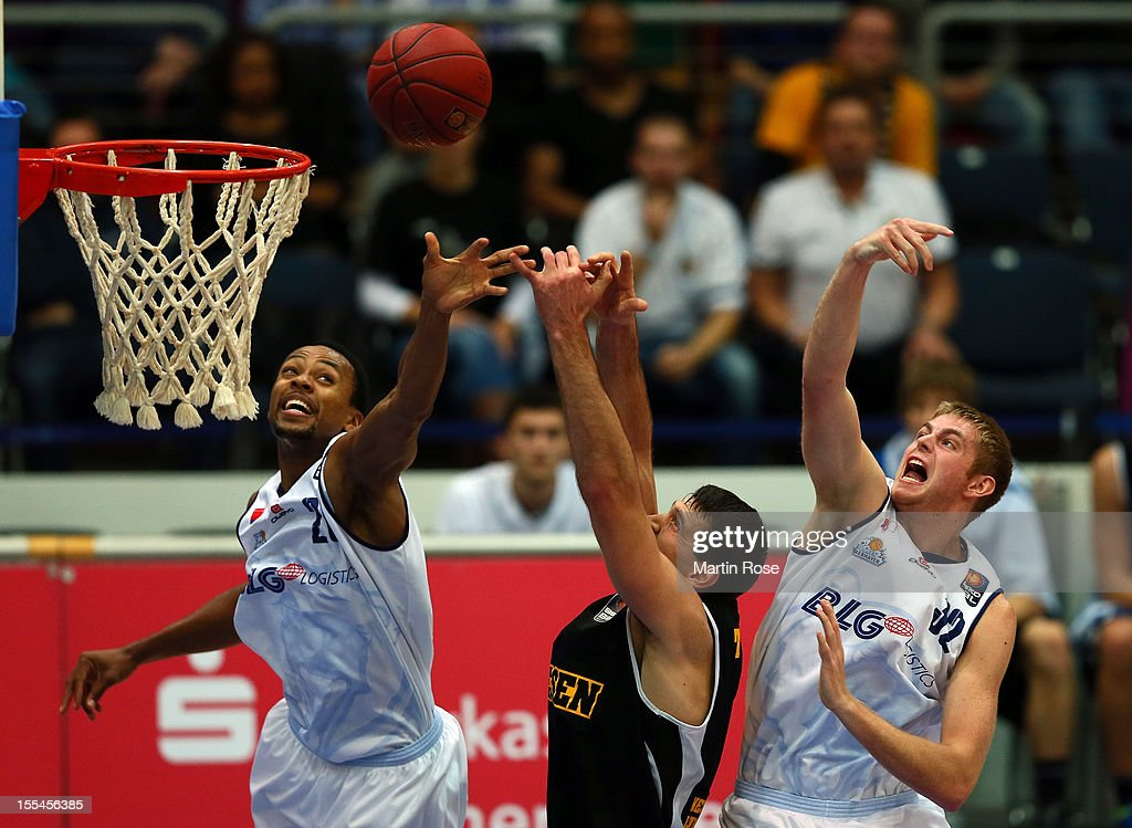 Alex Harris (L) and Justin Stommes (R) of Bremerhaven challenge for the ball with John Turek (C) of Ludwigsburg during the Beko BBL basketball match between Eisbaeren Bremerhaven and Nackar RIESEN Ludwigsburg at the Stadthalle on November 4, 2012 in Bremerhaven, Germany.