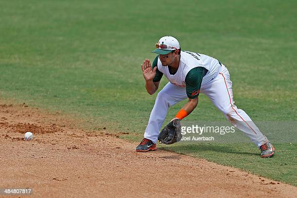 Alex Hernandez of the Miami Hurricanes fields the ball hit by Eric Hess of the Pittsburgh Panthers on April 13 2014 at Alex Rodriguez Park at Mark...