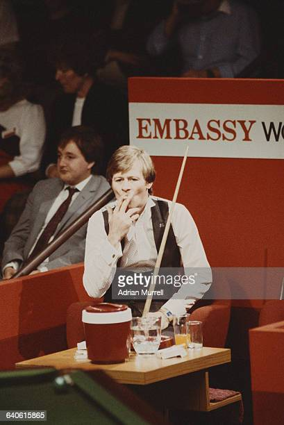 Alex Higgins of Northern Ireland smokes a cigarette during his World Snooker Championship Final match against Steve Davis on 2 May 1983 at the...