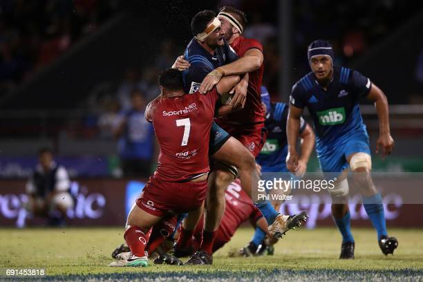 Alex Hodgman of the Blues is tackled during the round 15 Super Rugby match between the Blues and the Reds at Apia Park National Stadium on June 2...