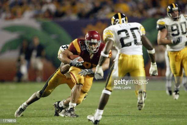 Alex Holmes of USC runs after the catch as Bob Sanders of Iowa makes the tackle during the FedEx Orange Bowl at Pro Player Stadium on January 2, 2003...