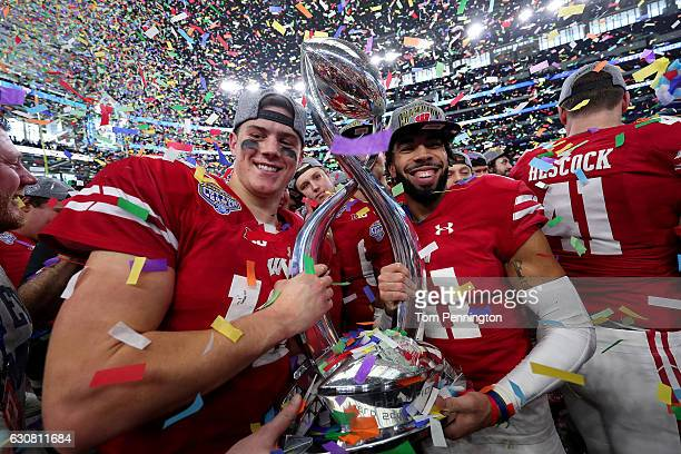 Alex Hornibrook of the Wisconsin Badgers and Jazz Peavy of the Wisconsin Badgers celebrate with the trophy after the Wisconsin Badgers beat the...
