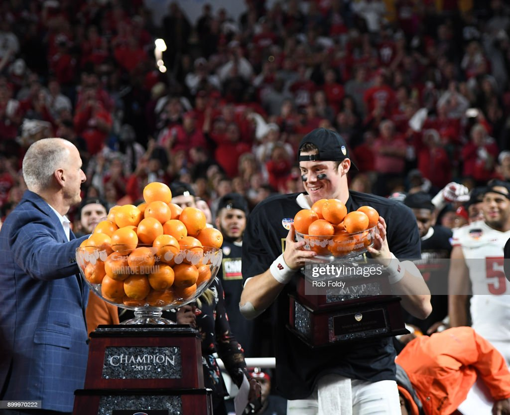 Alex Hornibrook #12 of the Wisconsin Badgers is awarded the MVP trophy following the 2017 Capital One Orange Bowl against the Miami Hurricanes at Hard Rock Stadium on December 30, 2017 in Miami Gardens, Florida.