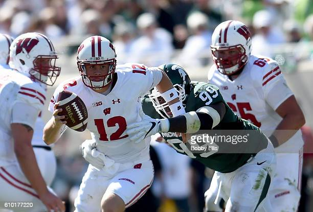 Alex Hornibrook of the Wisconsin Badgers is grabbed by Raequan Williams of the Michigan State Spartans as he runs downfield during the game at...