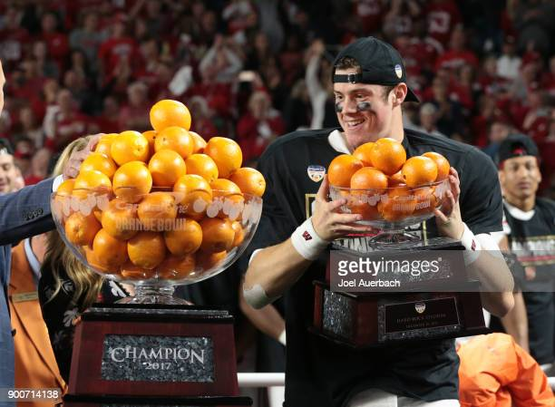 Alex Hornibrook of the Wisconsin Badgers looks at the championship trophy after being awarded the MVP trophy after the win against the Miami...