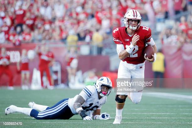 Alex Hornibrook of the Wisconsin Badgers runs for a first down after breaking a tackle against Sione Takitaki of the BYU Cougars in the fourth...