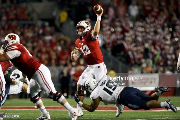 Alex Hornibrook of the Wisconsin Badgers throws a pass while being hit by Ian Togiai of the Utah State Aggies in the second quarter at Camp Randall...