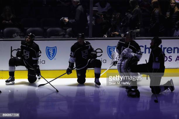 Alex Iafallo Dustin Brown Jonathan Quick and Jake Muzzin of the Los Angeles Kings look on during a ceremony honoring one thousand games played in the...