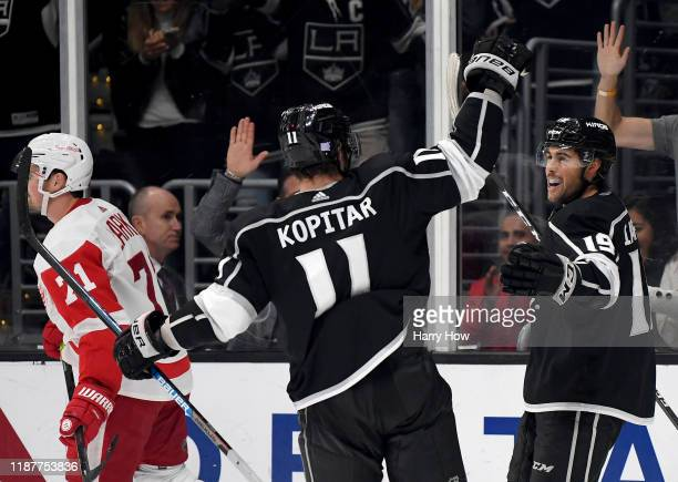 Alex Iafallo of the Los Angeles Kings celebrates his game winning goal with Anze Kopitar as Dylan Larkin of the Detroit Red Wings skate by during a...