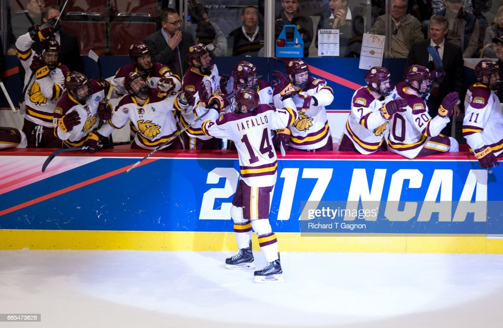 Alex Iafallo #14 of the Minnesota Duluth Bulldogs celebrates with his teammates after he deflected the puck past Merrick Madsen #31 of the Harvard Crimson for the winning goal with 26 seconds remaining during game one of the 2017 NCAA Division I Men's Hockey Frozen Four Championship Semifinal at the United Center on April 6, 2017 in Chicago, Illinois. The Bulldogs won 2-1.