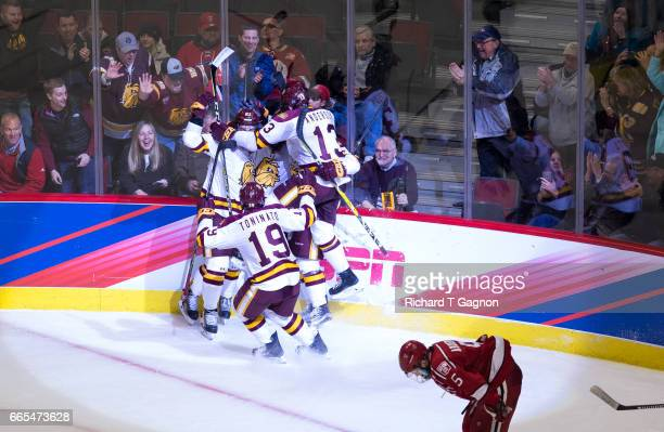 Alex Iafallo of the Minnesota Duluth Bulldogs celebrates with teammates Willie Raskob, Dominic Toninato and Carson Soucy after he deflected the puck...