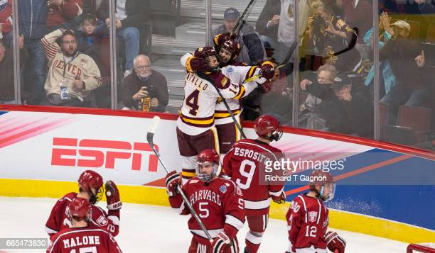 Alex Iafallo of the Minnesota Duluth Bulldogs celebrates with teammate Willie Raskob after he deflected the puck past Merrick Madsen of the Harvard...