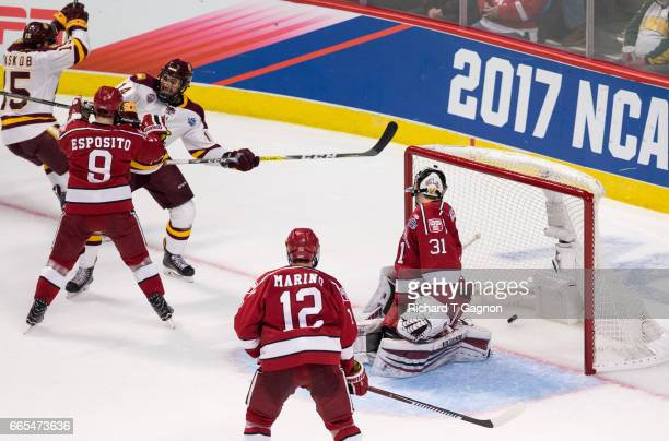 Alex Iafallo of the Minnesota Duluth Bulldogs deflects the puck past Merrick Madsen of the Harvard Crimson for the winning goal with 26 seconds...
